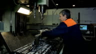 A worker removes detail from machine and check it video