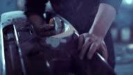 Worker sanding bodywork in auto repair garage video