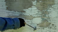 Worker scrubbing off peeling paint video