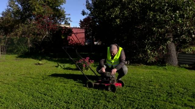 Worker starting lawn mower video