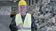 SLO MO worker sweeping the floor in a recycling facility video