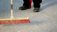 Worker sweeps the floor with a wide broom video