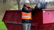 Worker talking on smart phone and keeps garbage bag on waste container video