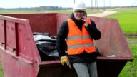 Worker talking on smart phone near waste container video