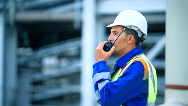 Worker talking on the radio, industrial scene in background video