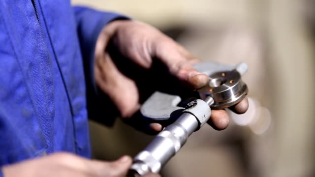 Worker the item is measured with a micrometer video