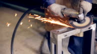 Worker using industrial grinder on metal parts in industrial plant, factory video