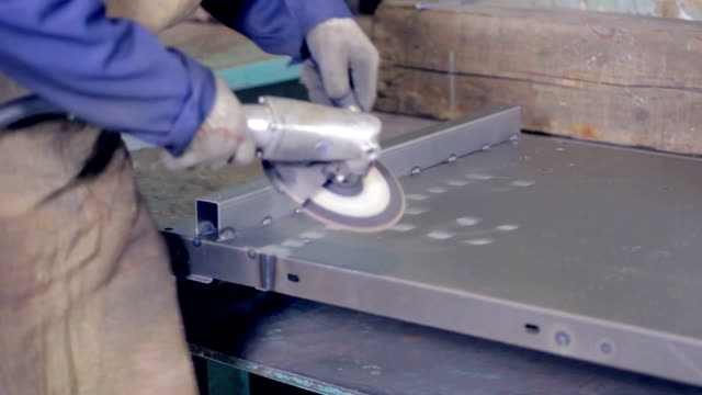 Worker using industrial grinder operating with metal at a metal processing plant video
