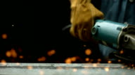 Worker using industrial grinder, slow motion video