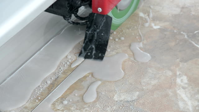 Worker wearing latex gloves cuts ceramic tiles with a wet tile saw. video
