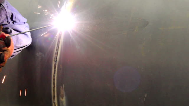 Worker weld storage tank in production video