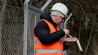 Worker with food near wire fence video