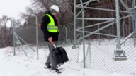 Worker with snow shovel near broken fence video