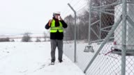 Worker with snow shovel walking near fence and start drink tea video