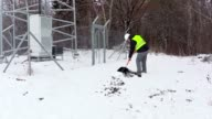 Worker with snow shovel working near fence video