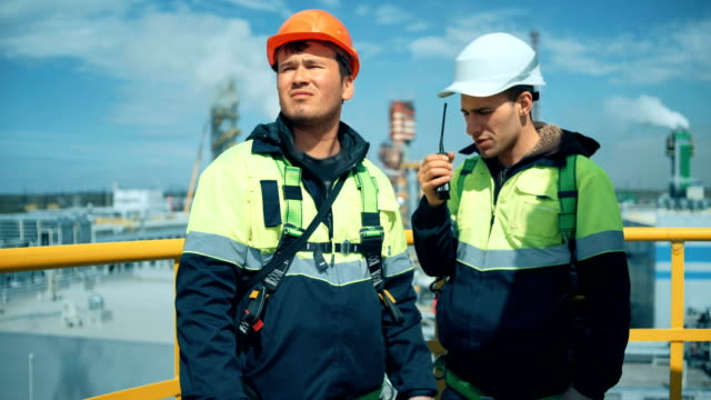 Worker with walkie talkie on industrial plant video