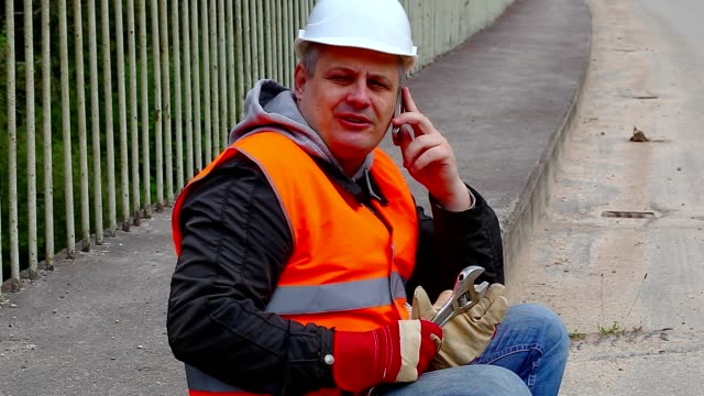 Worker with wrench and a telephone on the bridge video