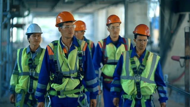workers and engineers, walking on industrial factory. video