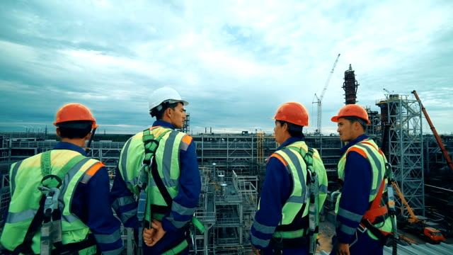 Workers at refinery as team discussing, industrial scene in background. video