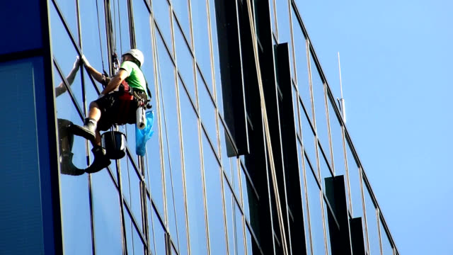 Workers cleaning windows on office skyscraper video
