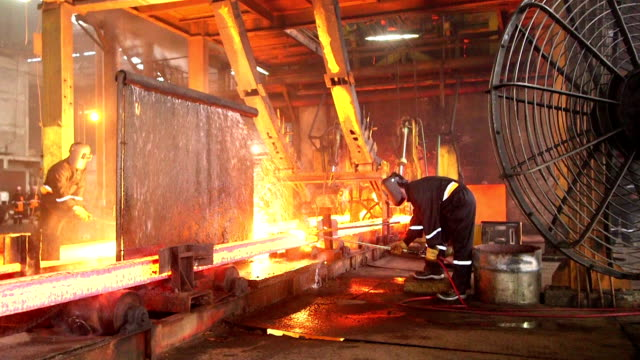 Workers cutting fiery steel blocks video