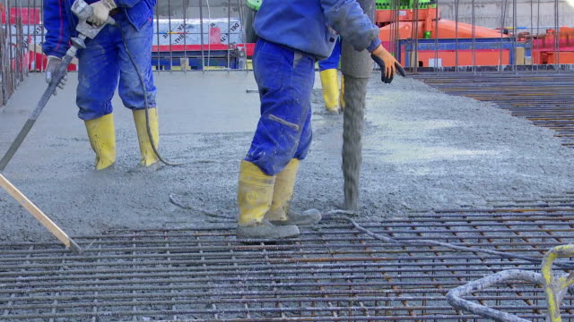 Workers Directing Concrete Onto The Construction Site TL video