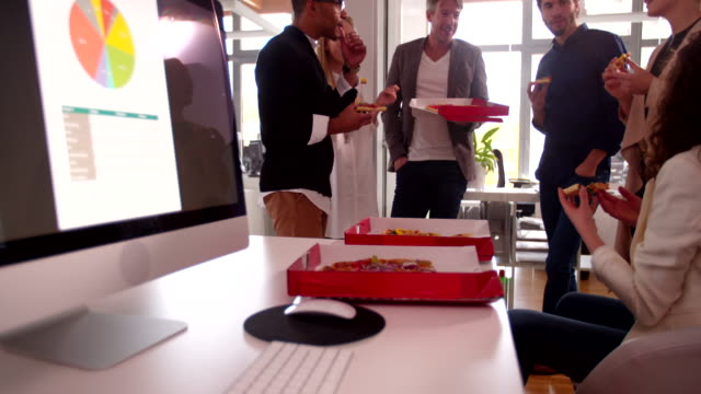 Workers  discussing concepts whilst eating pizza for a group meeting video