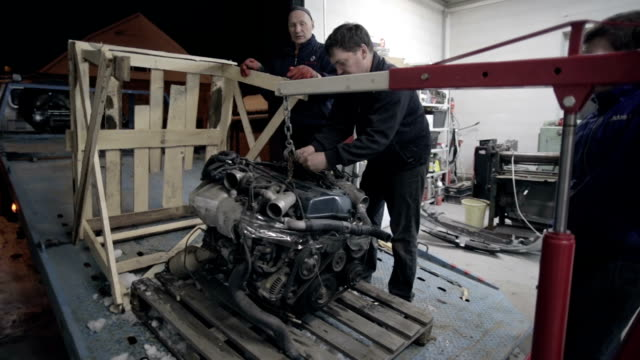 Workers group put the car engine on the truck video