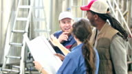 Workers in a micro brewery, discussing plans video