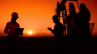 Workers in an Oilfield at Sunset video