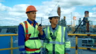 Workers in production plant as team discussing, industrial scene in background video