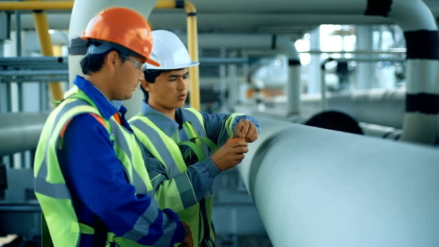 Workers measuring a tube with a tape measure. Industrial back ground with gas pipiline video