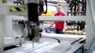 Workers operating factory machinery in warehouse video