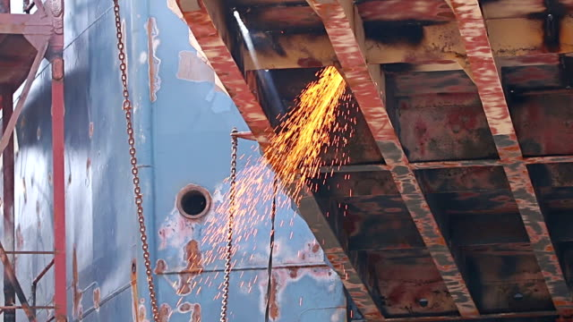 Workers polishing and welding during reparation of ship in shipyard video