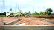 workers pouring cement foundation for house building (defocused) video