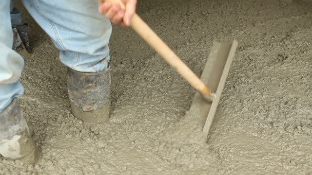 Workers Using Spreader Tools to Distribute Concrete video