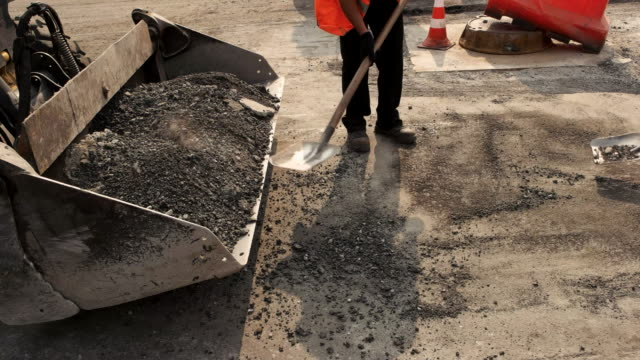 Workers with shovels throwing asphalt. video