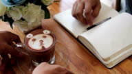 Working and drinking  a cup of art latte at coffee shop video