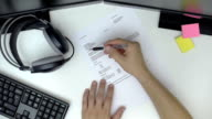 Working at home office desk and reading carefully a contract, top view video
