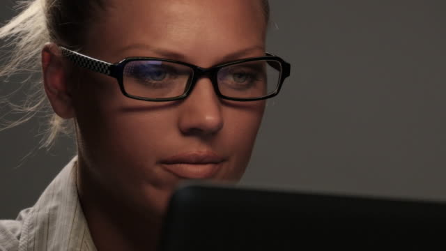 Working Late Woman With Glasses Using Computer at Night, Lit by Colored Lights video