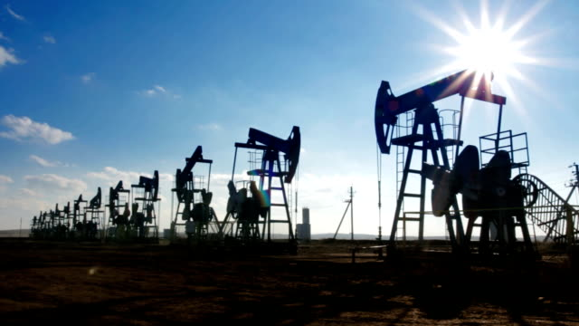 working oil pumps silhouette against sun video