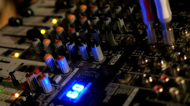 DJ works on the mixer console in night club video