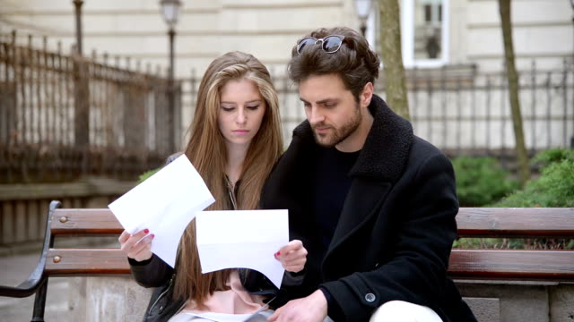 Worried couple reading a letter at home video