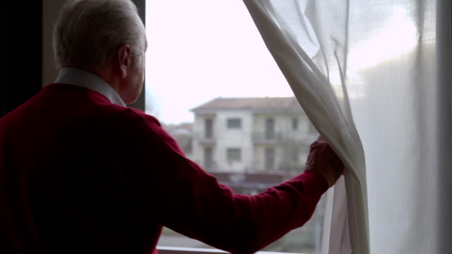 Worried elderly man moving the curtain and looking out the window video
