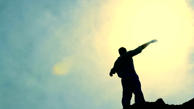 Worship Pose Colorful Silhouette of Man on Mountain Raising Arms video