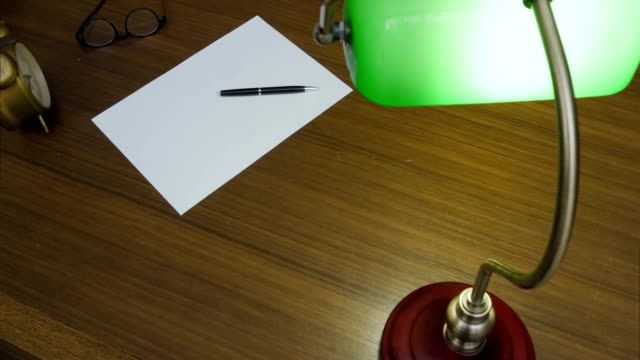 Writer's table with books, clock, glasses, clean sheet of paper and green lamp turned on video
