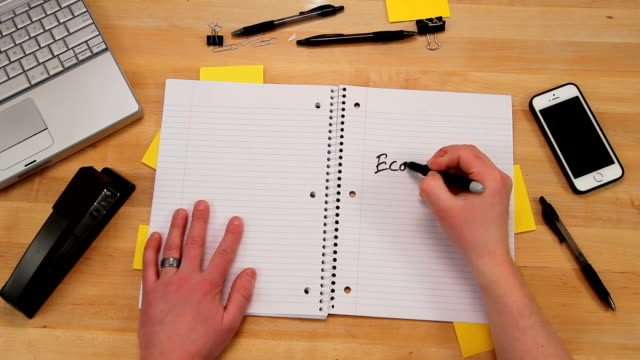 Writing economy is down in notebook, top view video