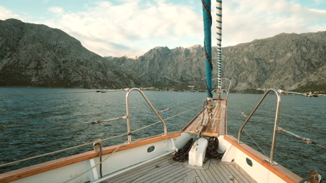 Yacht approaching the sea to the high mountains in sunny weather video