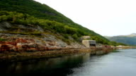 Yacht sailing along green hilly coast with pillbox of second world war in calm waters somewhere in Norway video