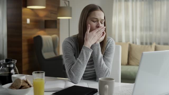 Yawning woman using laptop video
